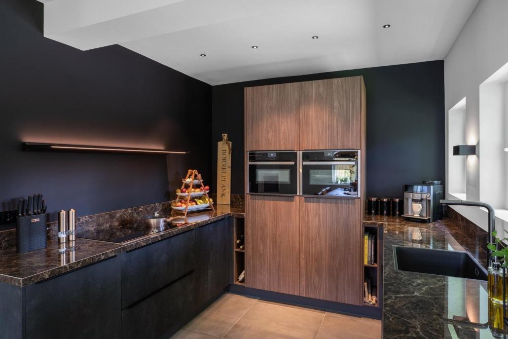Moderne strakke donkere keuken met houten kastenwand